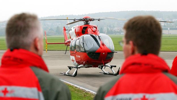 Rega-Mitarbeiter beobachten die Landung eines ihrer Rettungshelikopters.