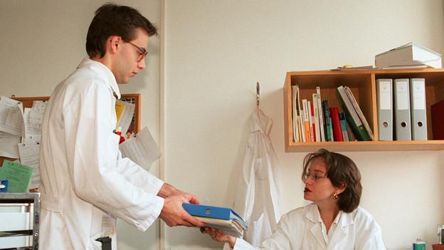 Ein Assistenzarzt übergibt einen Fall an eine Kollegin.