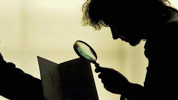 Eine Schattenfigur untersucht mit der Lupe ein Dokument