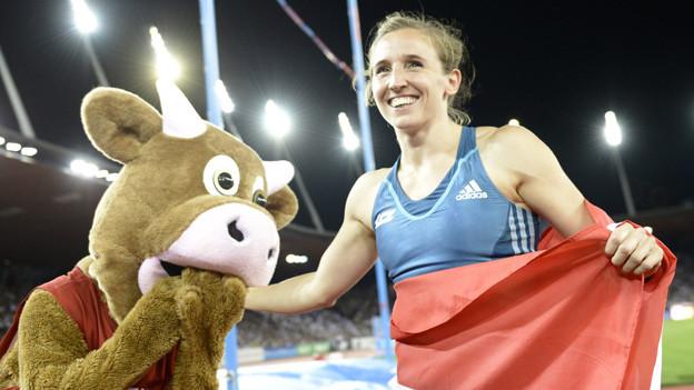 Stabhochspringerin Nicole Büchler mit Schweizer Fahne und dem Mascottchen Cooly