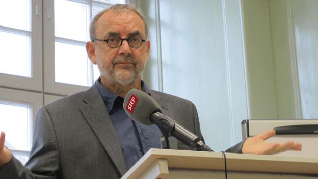 Ein Mann mit Brille und Kinnbart spricht in ein Mikrofon.