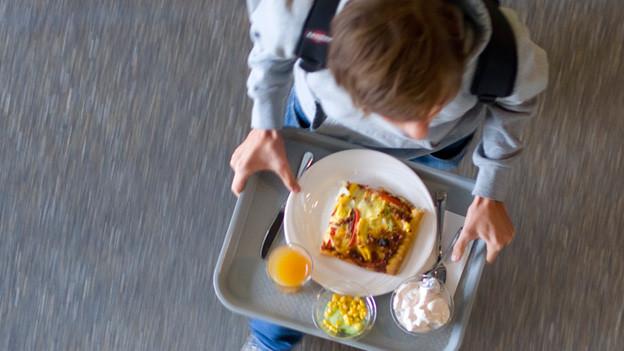 Ein Schüler trägt ein Tablett mit Essen.