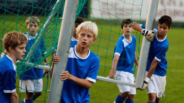 Nachwuchs-Fussballspieler stellen ein Goal auf.
