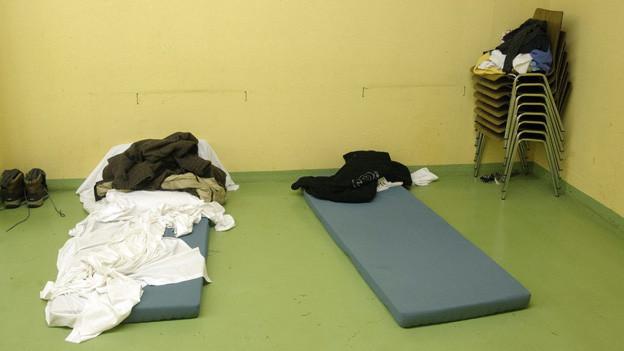 Zwei Matrazen liegen auf dem Boden eines kargen Raums.