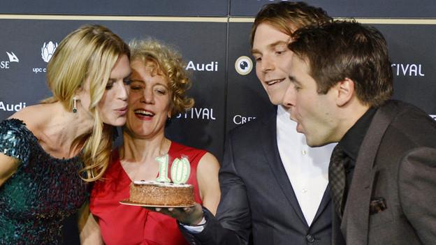 Eine Frau und ein Mann blasen die Kerzen auf einem Kuchen aus, der von einem weiteren Mann gehalten wird.