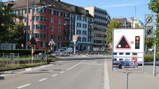 Ein Plakat macht Autofahrer auf einen Bahnübergang aufmerksam.