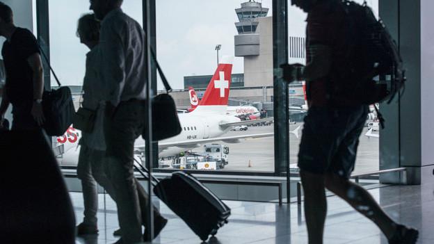 Ein Mann zieht einen Koffer, dahinter ein Flugzeug der Swiss.