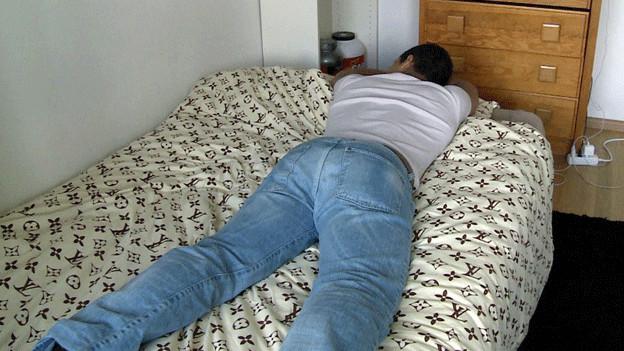 Ein Jugendlicher liegt auf dem Bett