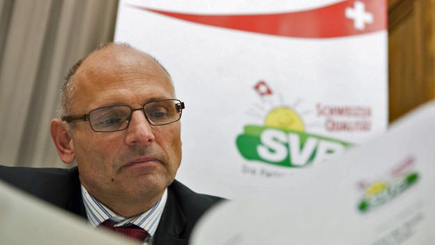 SVP-Präsident Alfred Heer blättert vo dem SVP-Logo in den Unterlagen