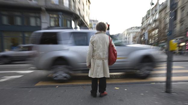 Eine Frau wartet am Fussgängerstreifen während ein Auto vorbeifährt.