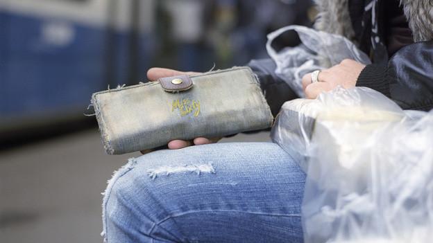 Eine Frau in zerschlissenen Jeans sitzt an einer Tramhaltestelle.