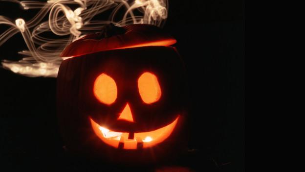 erleuchteter Halloween-Kürbis bei Nacht, im Hintergrund Kerzenrauch