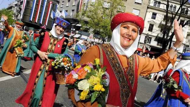 Eine Frau im mittelalterlichen Kostüm am Sechseläuten-Umzug.