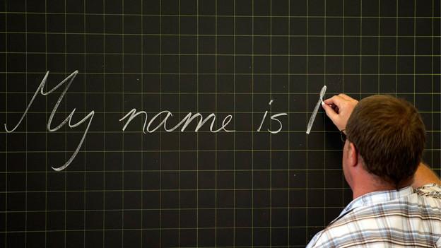 Ein Lehrer schreibt auf Englisch an eine Wandtafel.