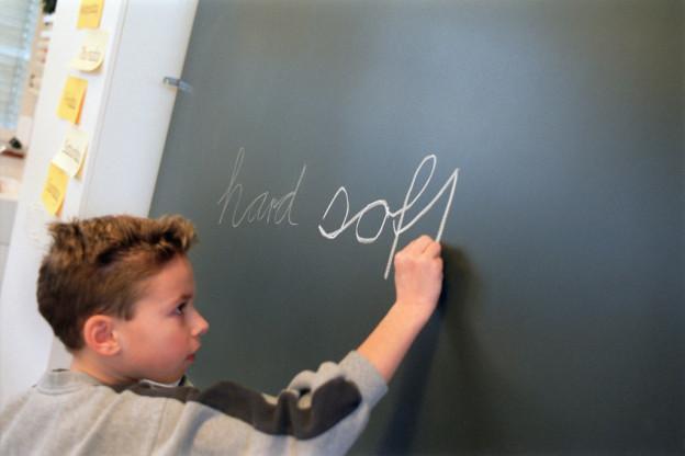 """Ein Junge schreibt das englische Wort """"hard"""" an die Wandtafel."""