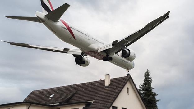 Ein Flugzeug überfliegt Dächer eines Wohngebietes