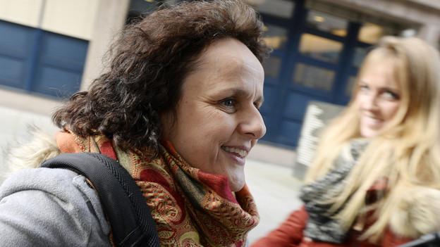 Iris Ritzmann mit einem Lächeln im Gesicht auf dem Weg ins Gericht.