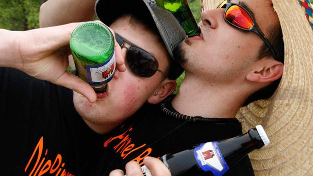 Zwei Jugendliche liegen auf einer Wiese und trinken Bier.