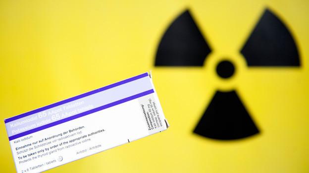 Eine Packung Jodtabletten vor gelbem Hintergrund mit dem Atomzeichen.
