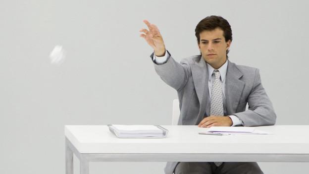 Ein Mann wirft ein zerknülltes Papier weg