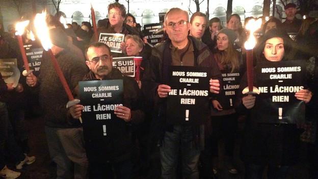 """Eine Menschenmenge mit Fackeln und schwarzen Plakaten, darauf: """"Nous somme Charlie"""""""