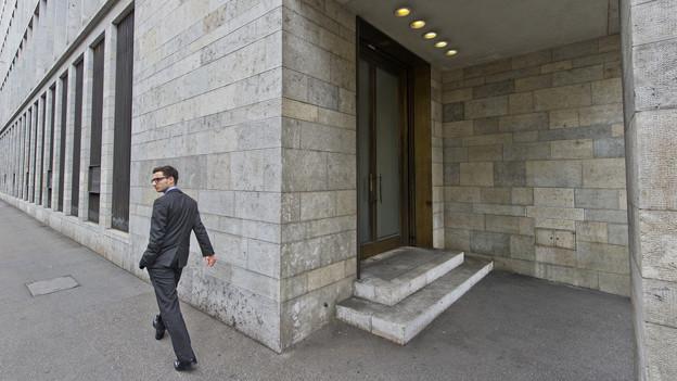 Ein Mann in grauem Anzug geht an einer Bank vorbei