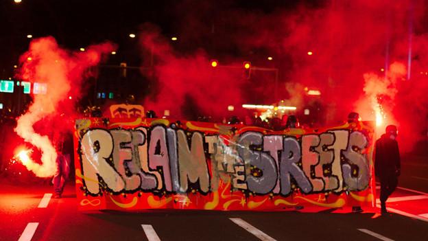 Der Auftakt der Krawalle: Vermumte halten ein Transparent mit der Aufschrift Reclaim the Streets
