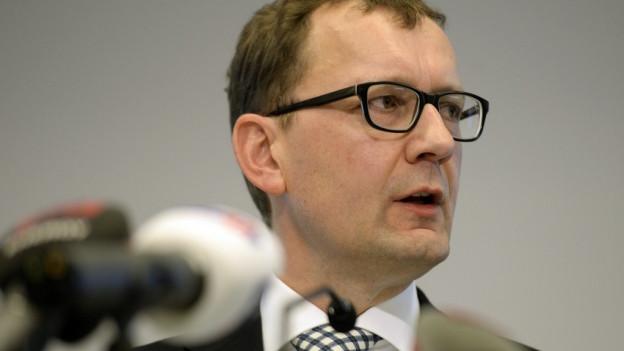 Der Kopf von Peter Meier hinter einer Reihe von Mikrofonen.