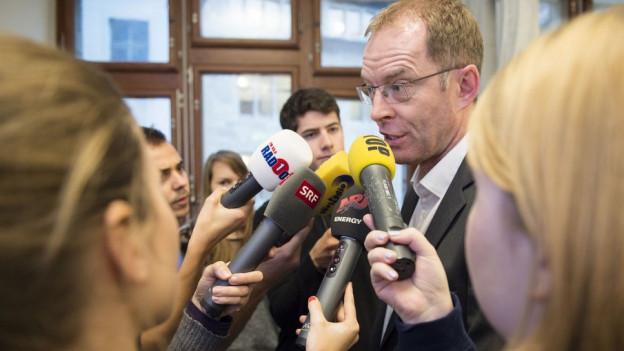 Journalisten mit Mikrofonen umlagern Mann mit Brille
