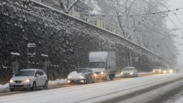 Autokolonne im Schneefall in der Stadt Zürich.