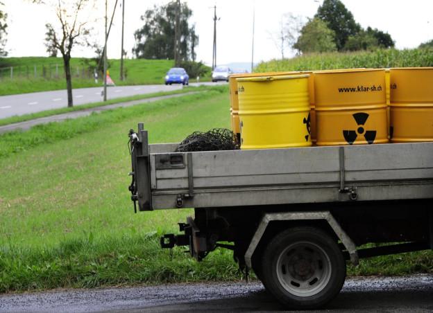 Gelbe Fässer mit dem Atomzeichen auf einem Wagen.
