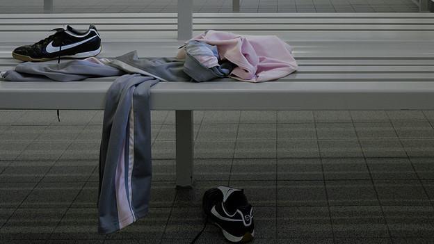 Garderobe einer Turnhalle mit Kleidern eines Kindes (Symbolbild)
