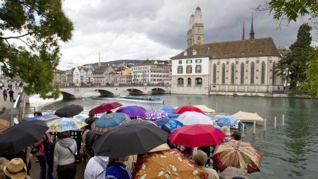 Leute unter Regenschirmen schauen über die Limmat zur Wasserkirche
