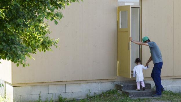 Das beschleunigte Asylverfahren funktioniert. Ein Mann und ein Kind betreten eine Unterkunft im Asylzentrum Juch der Stadt Zürich.
