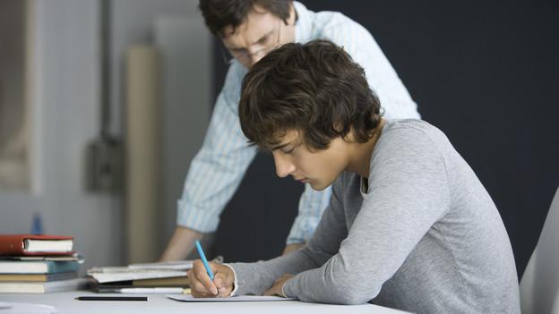 junger Mann schreibt am Tisch, Lehrer schaut ihm über die Schulter
