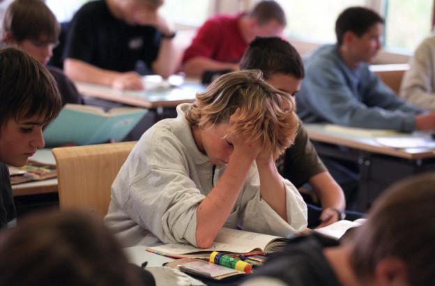 Schulklasse am arbeiten, ein Schüler stützt den Kopf auf.