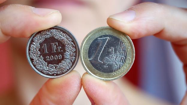 ein Frankenstück und ein Euro zwischen Fingern