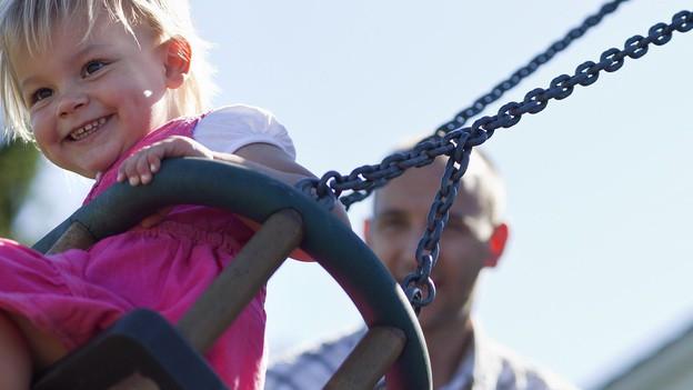 Ein Kind auf einer Schaukel, dahinter der Vater.