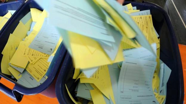 Kisten voller blauer und gelber Wahlzettel