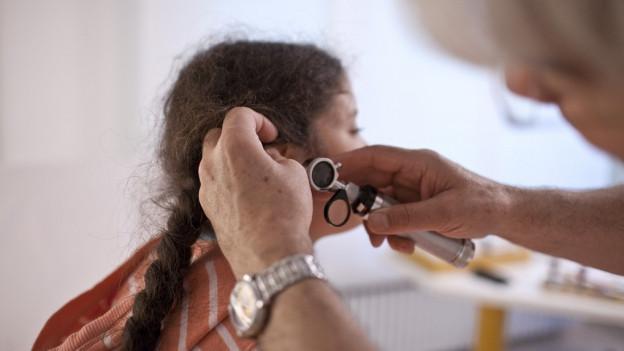 Arzt schaut einem Kind ins Ohr
