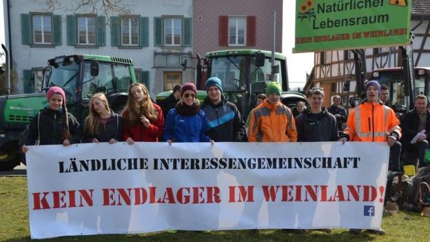 Eine Reihe junger Leute hält ein Tramparent mit der Aufschrif Ländliche Interessengemeinschaft: kein Endlager im Weinland. Im Hintergrund grosse Traktoren.