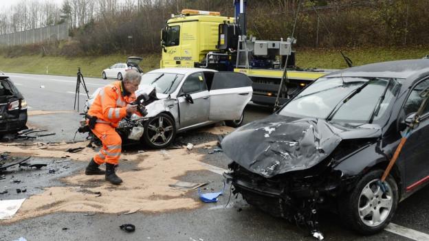 Ein Polizist fotografiert nach einem Unfall auf der A1 drei Autowracks.