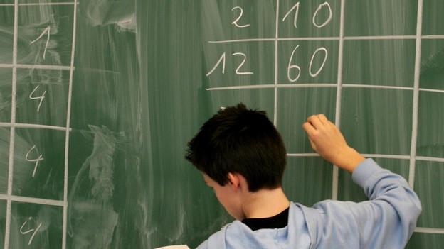 Ein Schüler schreibt Zahlen an eine Wandtafel
