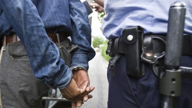 Ein Polizist verfrachtet einen Mann in Handschellen in eine Fahrzeug.