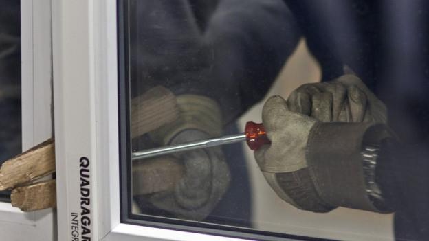 ein Mann wuchtet mit einem Schraubenzieher ein Fenster auf