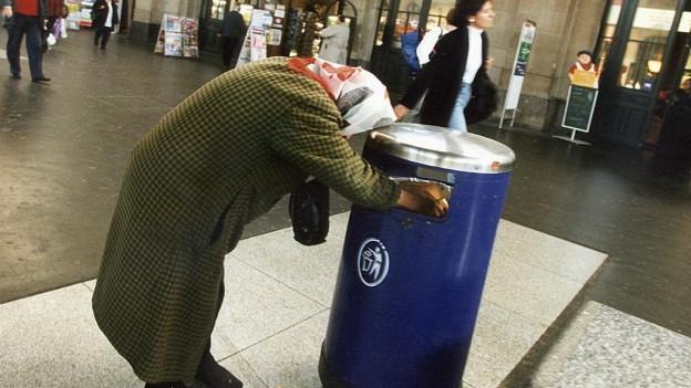 Eine alte Frau durchsucht einen Abfallkorb im Zürcher HB