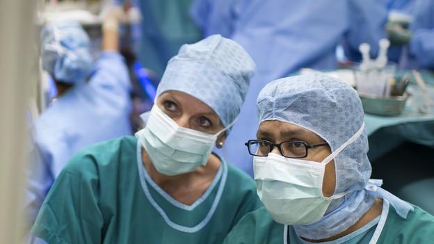 Eine Chirurgin und ein Chirurg sehen sich gemeinsam Patientendaten an