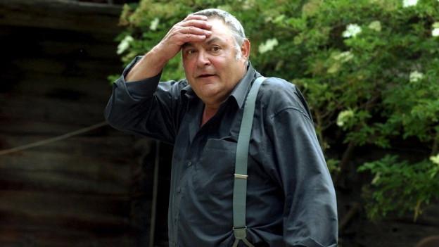 Ein Mann in Hosenträgern greift mit der Hand an die Stirn.