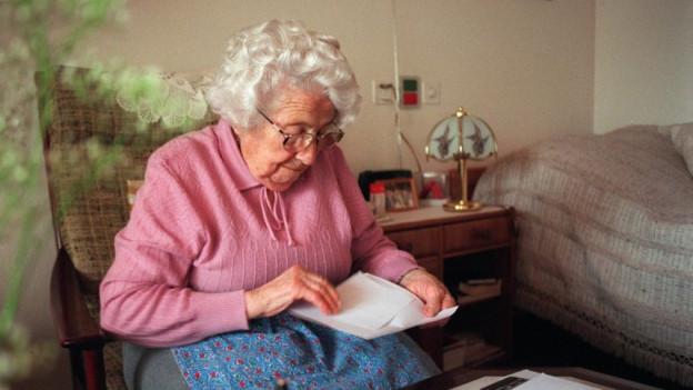 alte Frau liest in ihrem Zimmer