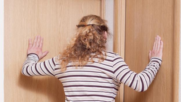 Eine Frau steht vor verschlossenen Türen